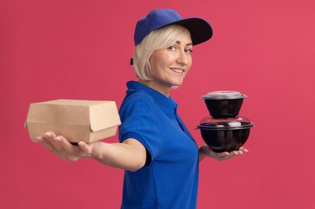 Lächelnde blonde lieferfrau und mütze, die in der profilansicht steht und sich ausstreckt