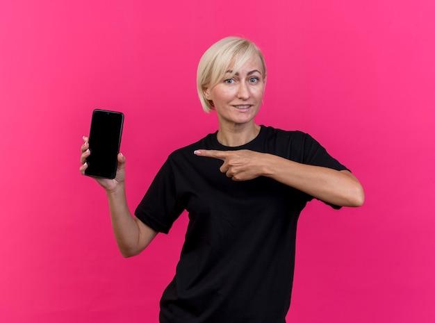 Lächelnde blonde slawische frau mittleren alters, die handy zeigt und auf es lokalisiert auf purpurroter wand zeigt