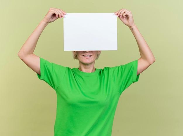 Lächelnde blonde slawische frau mittleren alters, die leeres papier vor augen lokalisiert auf olivgrüner wand hält
