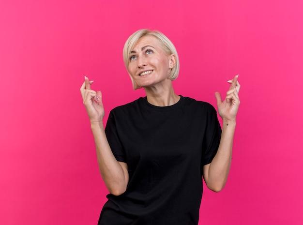 Lächelnde blonde slawische frau mittleren alters, die nach oben schaut und glücksgeste tut, lokalisiert auf purpurrotem hintergrund mit kopienraum