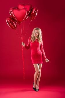 Lächelnde blondine, die großen haufen roter luftballons hält