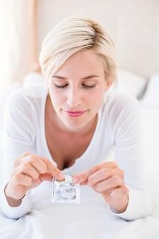 Lächelnde blondine, die kondom halten