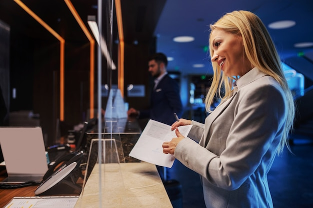Lächelnde blondine mittleren alters in abendgarderobe, die an der rezeption eines schicken hotels steht und eincheckt.