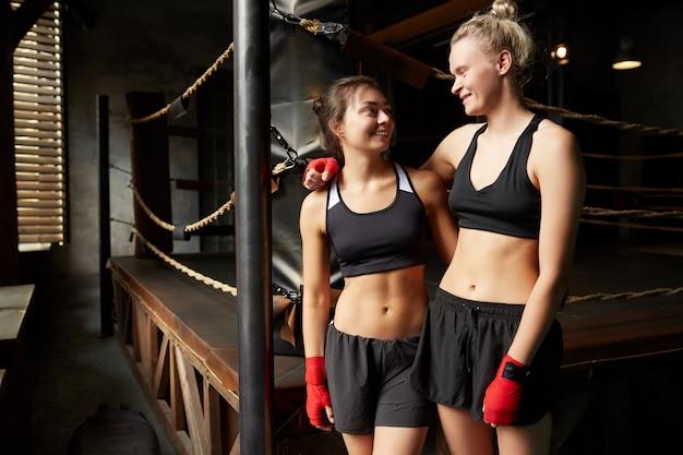 Lächelnde boxerinnen posieren am ring