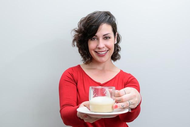 Lächelnde brasilianische frau, die eine tasse cappuccino hält und anbietet.