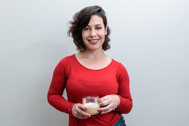 Lächelnde brasilianische frau vor der kamera und hält eine tasse cappuccino.