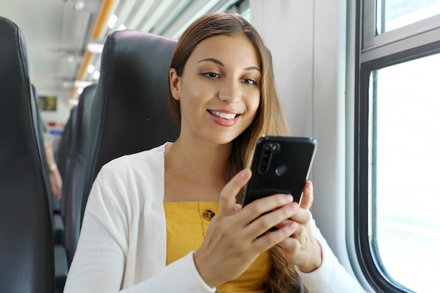 Lächelnde brasilianische geschäftsfrau mit smartphone-social-media-app beim pendeln zur arbeit im zug. frau, die im transport sitzt, der reise genießt.
