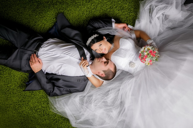 Lächelnde braut und bräutigam, die auf dem gras ähnlichen teppich liegen.