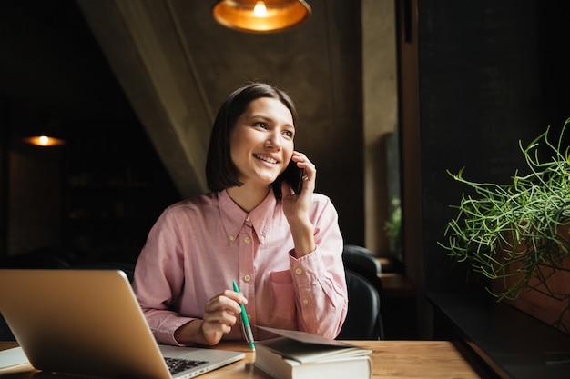 Lächelnde brünette frau, die durch den tisch mit laptop-computer sitzt