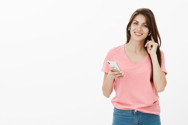 Lächelnde brünette frau, die im studio mit ihrem telefon und ohrhörern aufwirft