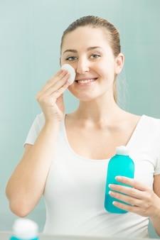 Lächelnde brünette frau, die in die reflexion schaut und lotion verwendet