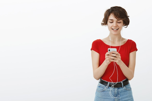 Lächelnde brünette frau, die sms auf telefon und musik in kopfhörern hört
