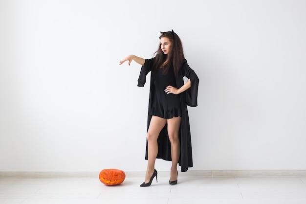 Lächelnde brünette frau im halloween-make-up, das mit geschnitztem kürbis über heller oberfläche mit kopienraum aufwirft