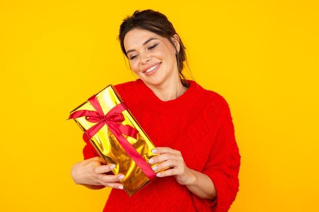 Lächelnde brünette frau mit großem geschenk im gelben studio.