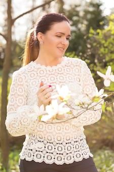 Lächelnde brünette frau mit nacktem make-up, die spitzenbluse trägt und in der nähe der blühenden magnolienblumen posiert