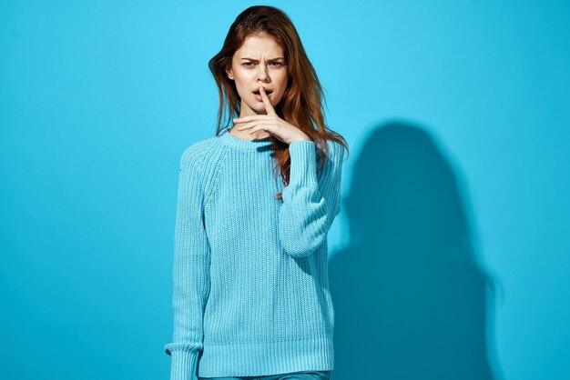 Lächelnde brünette im blauen pullover und in den jeansemotionen beschnittene ansicht isolierten hintergrund. hochwertiges foto
