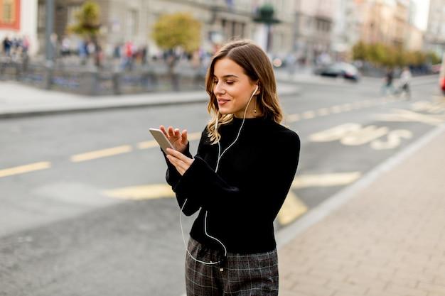 Lächelnde brunettefrau, die mobile bei der stellung auf straße und dem warten auf einen bus oder ein taxi verwendet