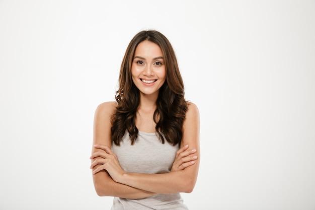 Lächelnde brunettefrau mit den gekreuzten armen, welche die kamera über grau betrachten