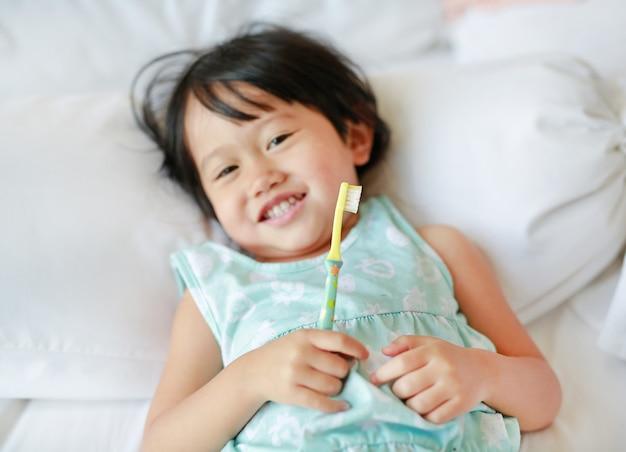 Lächelnde bürstende zähne des kindermädchens auf dem bett am morgen, fokus an ihrem gesicht.