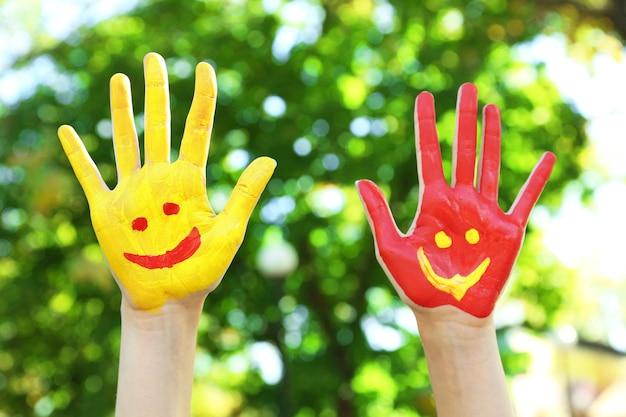 Lächelnde bunte hände über natürliche szene