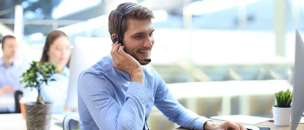 Lächelnde callcenter-mitarbeiter sitzen in einer reihe mit ihrem headset