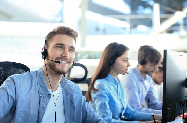 Lächelnde callcenter-mitarbeiter sitzen in einer reihe mit ihrem headset.