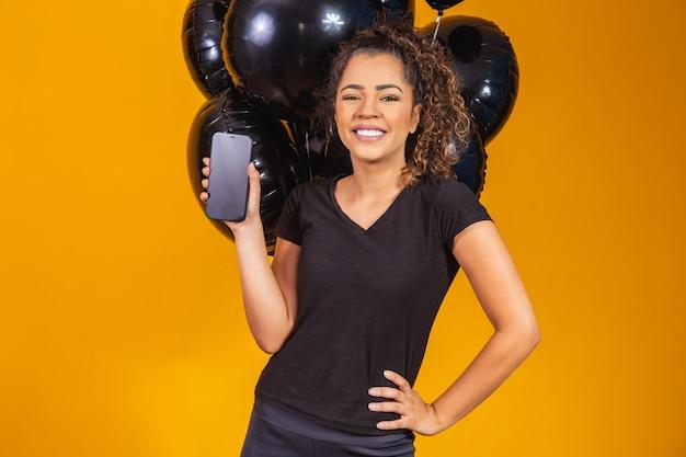 Lächelnde charmante junge afrofrau, die ein mobiltelefon mit leerem leerem bildschirm auf gelbem hintergrund mit luftballon-studioporträt hält. siedlung am schwarzen freitag