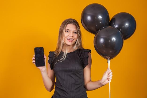 Lächelnde charmante junge frau, die ein mobiltelefon mit leerem leerem bildschirm auf gelbem hintergrund mit luftballon-studioporträt hält. siedlung am schwarzen freitag