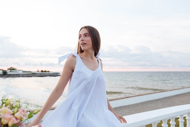 Lächelnde charmante junge frau im weißen kleid, das auf promenade sitzt