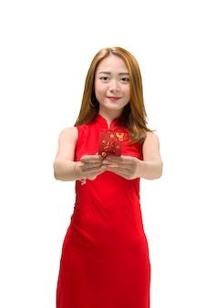 Lächelnde chinesische frau im cheongsam kleid, das rote umschläge anhält