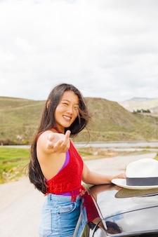 Lächelnde chinesische junge frau, die anbietet, ihr in der natur zu folgen