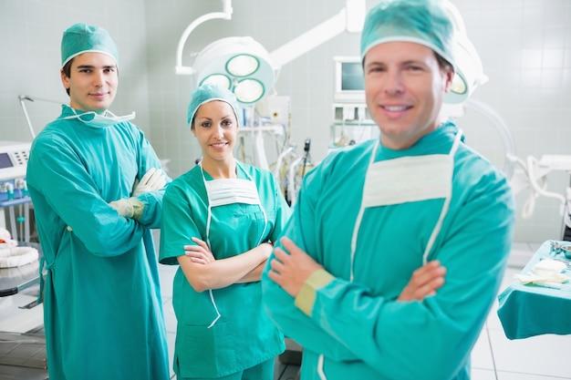 Lächelnde chirurgen, die kamera mit den gekreuzten armen betrachten