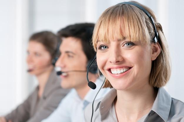 Lächelnde dame, die im callcenter-büro mit kollegen arbeitet