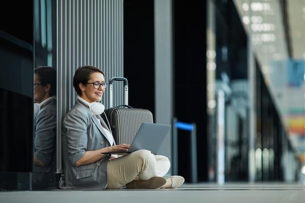 Lächelnde dame, die in der flughafenlobby arbeitet