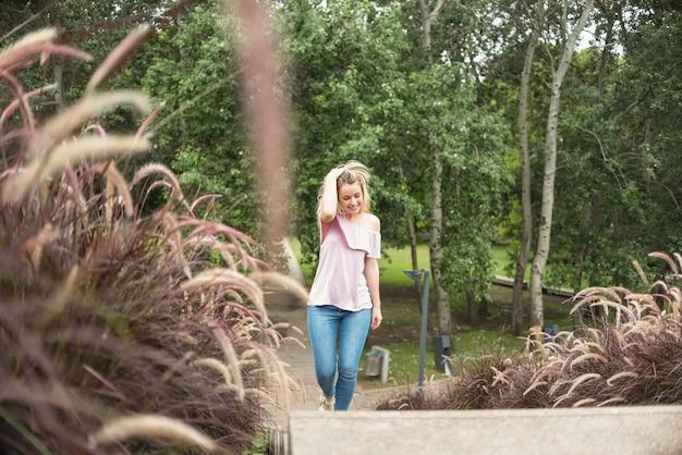 Lächelnde dame, die in stadtpark geht