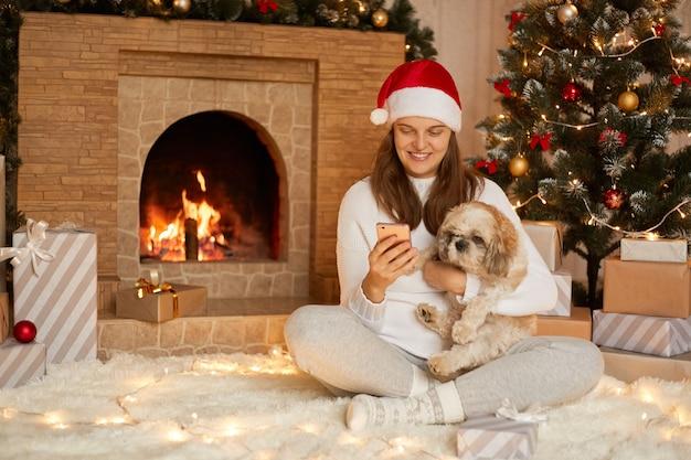 Lächelnde dame, die mit smartphone auf dem boden sitzt und ihren pekingese-hund umarmt, dame, die soziales netzwerk über handy überprüft, mit gekreuzten beinen sitzt, schaut lächelnd auf dem bildschirm des geräts.