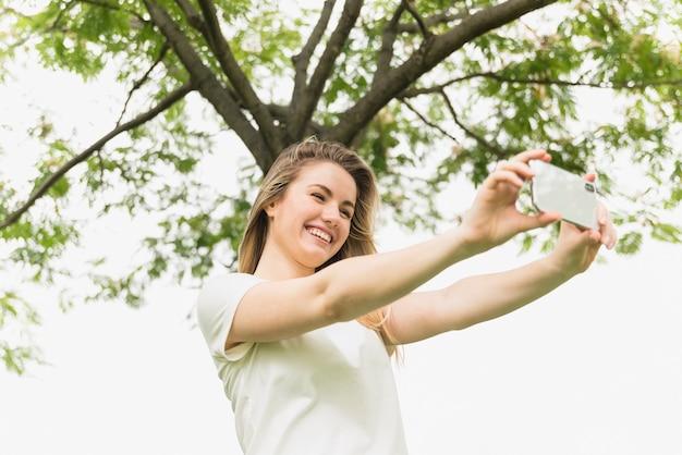 Lächelnde dame, die selfie am handy nahe baum nimmt