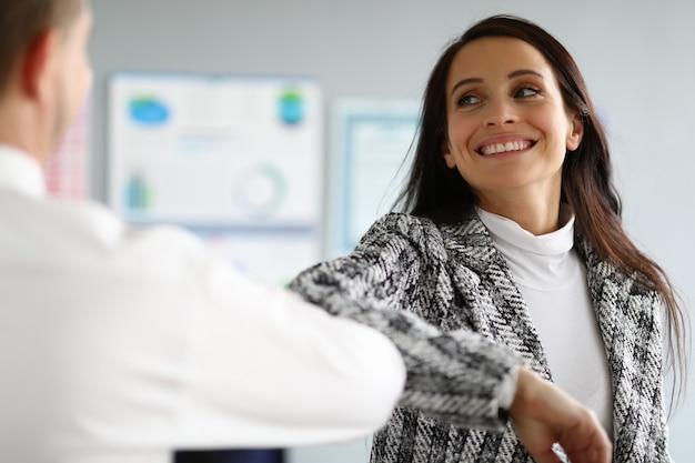 Lächelnde dame im anzug coronavirus händedruck