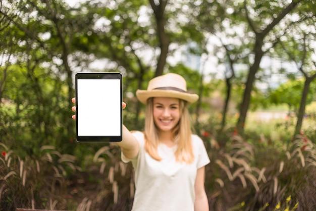 Lächelnde dame im hut, der tablette im park zeigt