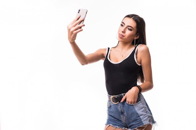 Lächelnde dame im schwarzen hemd machen selfie auf ihrem telefon isoliert