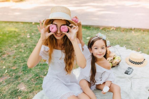 Lächelnde dame im weißen kleid hält rosa lebkuchen wie brille, sitzt auf decke mit tochter. hübsches kleines mädchen mit band, das neben scherzender mutter während des picknicks aufwirft.