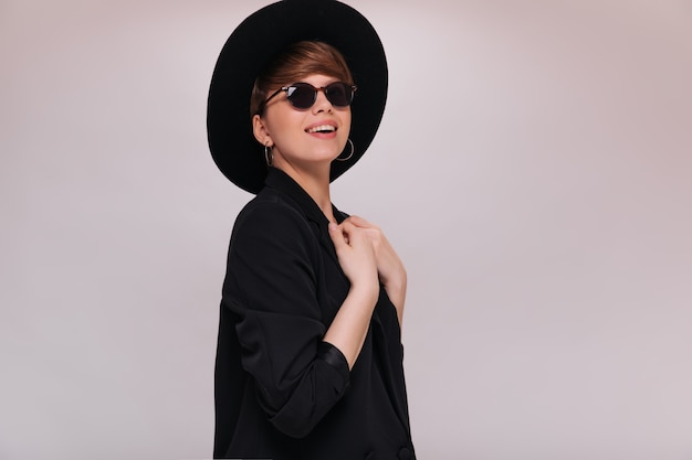 Lächelnde dame in brille und schwarzem hut, der auf weißem hintergrund aufwirft. fröhliche frau in der schwarzen jacke lächelt auf isoliertem hintergrund