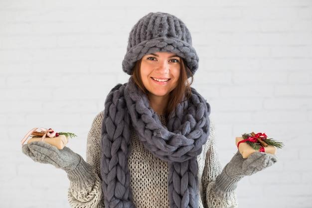 Lächelnde dame in den handschuhen, im hut und im schal mit geschenkboxen
