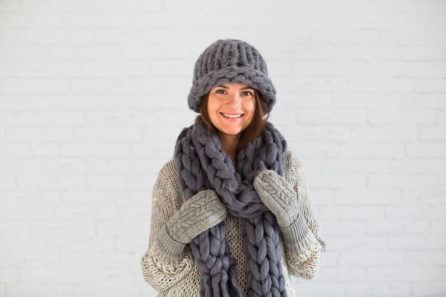 Lächelnde dame in handschuhen, mütze und schal