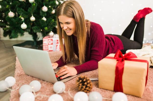 Lächelnde dame mit laptop nahe geschenkboxen, baumstumpf, lichterketten und weihnachtsbaum