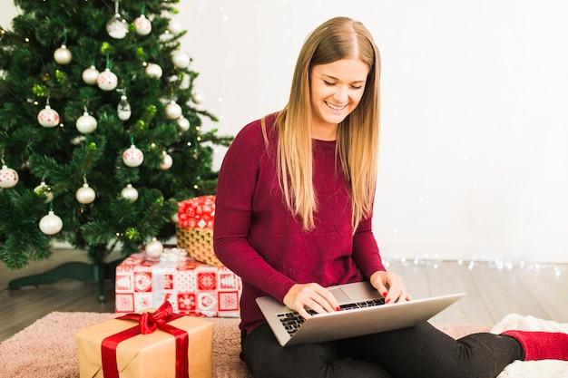 Lächelnde dame mit laptop nahe geschenkboxen und weihnachtsbaum