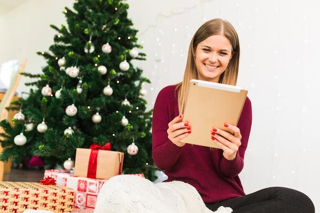 Lächelnde dame mit tablette nahe geschenkboxen und weihnachtsbaum