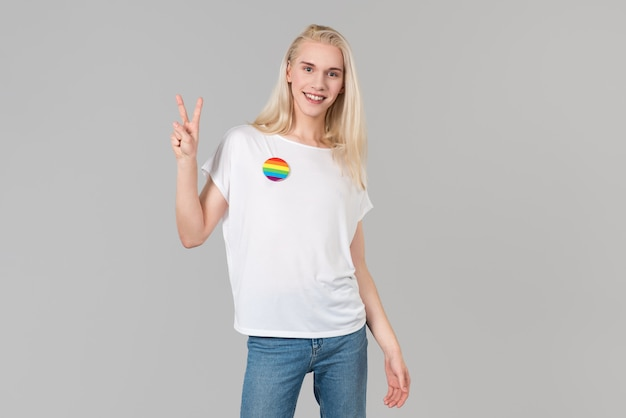 Lächelnde dame mit weißem t-shirt und siegessymbol