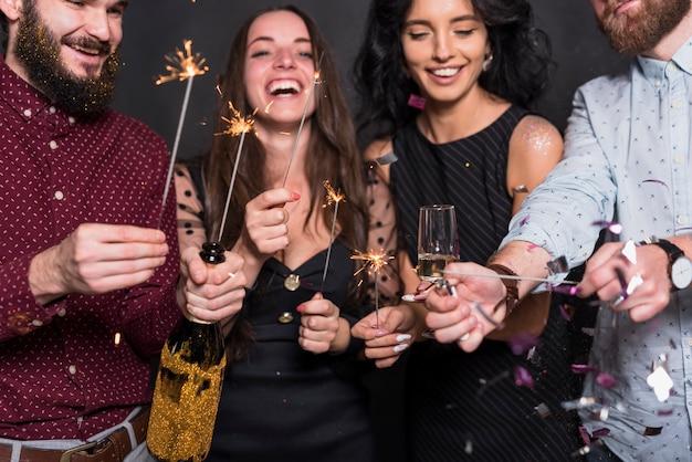 Lächelnde damen und kerle, die brennende bengallichter, -flasche und -glas des getränks halten