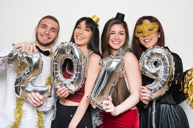 Lächelnde damen und mann in abendgarderobe mit ballonzahlen